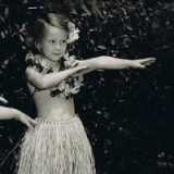 Early love of Hawaii - A preschool picture: a little haole girl in a little grass skirt on a little grass stage