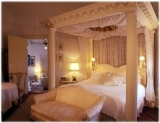 The White Room - A most romantic experience, sometimes called the bridal suite or special occasion suite, is on the second floor of the house. It offers a king sized bed with hand sewn canopy and lace accents throughout, a large bathroom with conventional tub and shower, and a small sitting area for reading or relaxing.