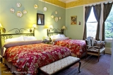 The English Room - The last of the four rooms located on the second floor. It is ideal for travelers with more than 2 people or in need of separate beds. One of the largest guest rooms in the house, it has 2 queen sized beds and has an abundance of natural light. The bath has a shower but no tub. Photo courtesy of Tracy Cox Photography
