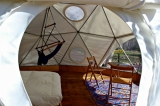 Inside the Geodesic domes - Our geodesic domes can accommodate up to 5-6 people but are typically equipped with a double bed, a fun swing from the ceiling, a small table and chairs, and towels and water for your convenience.