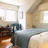 Minas Basin Suite - This beautifully decorated suite is located in the main-house on the second floor.  This room includes a luxurious queen-size bed, TV, desk and a large ensuite bathroom with a walk-in rain shower. The adjoining sitting room has a single sofa bed, rocking chair, TV and a cozy gas fireplace.