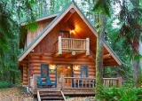 """Mt. Baker Lodging - Cabin 10 - This 2-story 2+bedroom 3/4-bath log home located directly across from the summer recreation area in the Snowline community says """"cabin in the mountains!"""". The 1st floor includes an open country kitchen and a living/dining area with a freestanding gas fireplace, a 3/4-bath, and a separate laundry area. The 2nd floor includes one large bedroom with 2-queen beds and a walk out balcony. A second divid"""