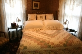 Rose Room - Pretty Rose has lace curtains and rose themed accessories. The full size bed is covered by an embroidered quilt. This beautiful, light and airy room overlooks the gardens below.