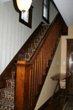 Main Staircase - Our Craftsman style main staircase leads upstairs to three rooms in our bed and breakfast: Iris, Rose, and Lily. Upstairs we serve hot coffee and our homemade biscotti first thing in the morning for early risers!